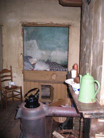 Huiskamer met bedstede en potkachel in het wevershuis